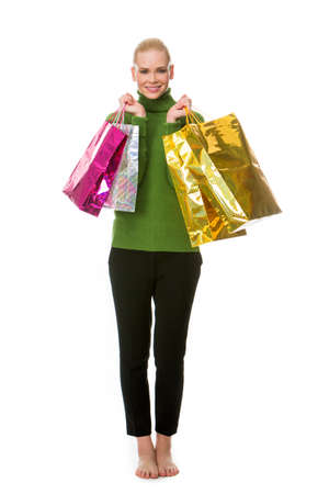 25 to 30 years old: blonde smiling woman carrying gift bags and looking at the camera Stock Photo