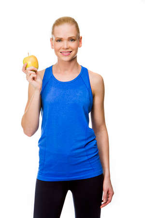 25 to 30 years old: smiling blonde woman wearing fitness clothing and holding an apple Stock Photo