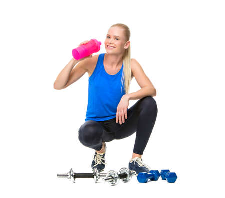25 to 30 years old: blonde woman wearing fitness clothing and drinking after exercising with weights