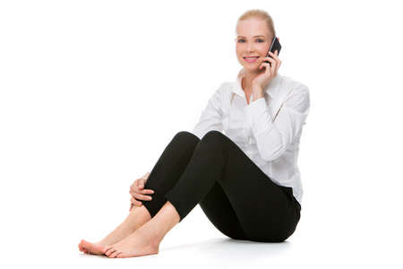 blonde smiling businesswoman seated on the floor and using mobile phone photo