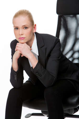 seated: blonde serious businesswoman seated on a chair with hands below chin