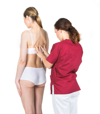 two person only: physiotherapist doing a physical examination of a woman