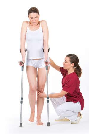 finer: Mujer con la muleta en la fisioterapeuta haciendo piernas rehabilitaci�n
