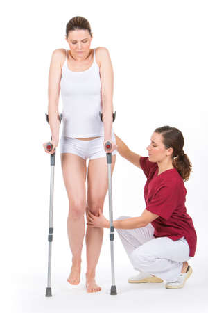 finer: woman with crutch at the physiotherapist doing legs rehabilitation