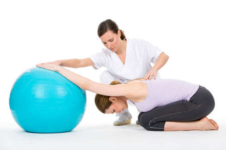 woman with physiotherapist exercising and reinforcing the vertebral column