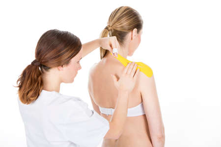finer: Physiotherapist applying tapes on a shoulder