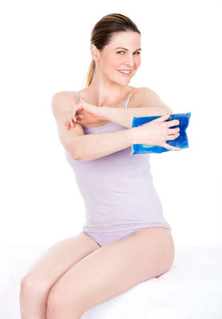 woman with cold hot pack on elbow for therapeutic relief