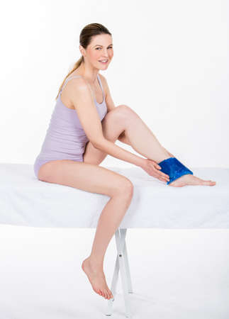 25 30 years: woman with ice pack on ankle Stock Photo