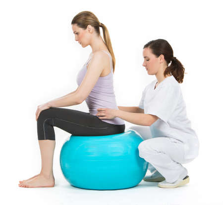 physiotherapy: doctor with medical ball and woman patient Stock Photo