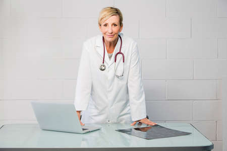 50 to 55 years: woman doctor standing behind desk Stock Photo