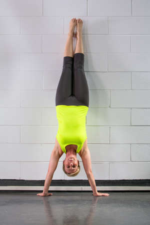 middle age woman doing handstand across wall