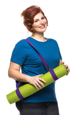 curvy woman carrying yoga mat on the white background