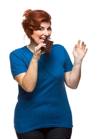 curvy woman eating chocolate tablet on the white background
