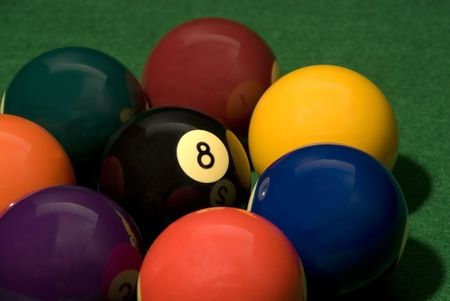 Eight ball in the middle of other pool balls on the table Stock Photo