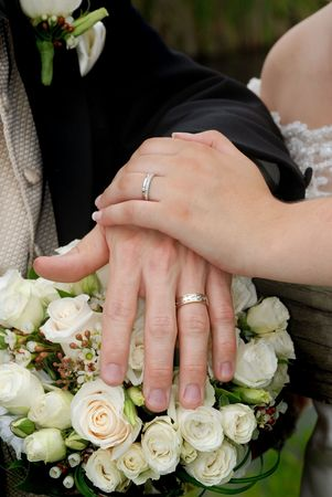 gold wedding ring on white roses bouquet Stock Photo - 3412924