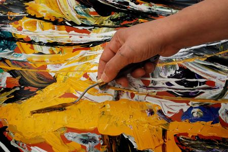 Woman hand painting in yellow  with spatula Stock Photo