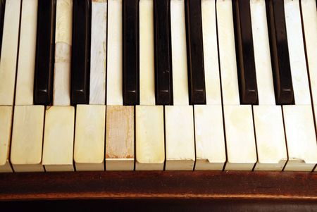 very old wooden piano with ivory keys broken and scratched Stock Photo