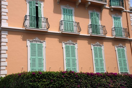 Green window shutter on luxury pink house photo
