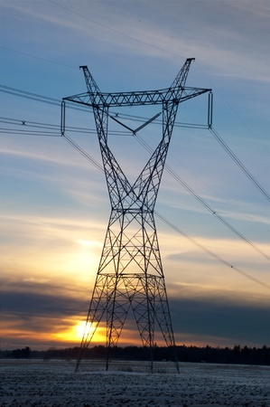 Silhouette of a electric high voltage steel pylone at sunset in winter