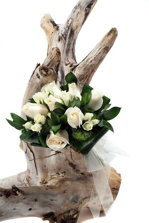 A wedding bouquet of flowers on white on tree stump