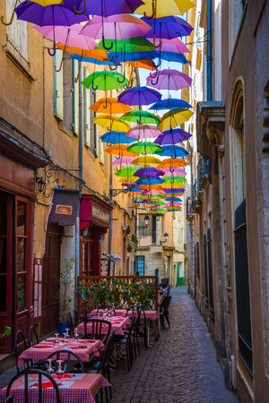 Historic alley and restore ziers in France in the shade of umbrellas Stock Photo