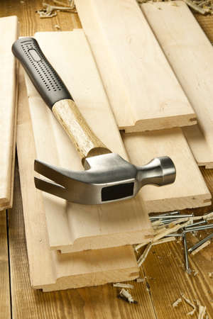 carpenter's sawdust: Hammer and nails are on a wooden planks