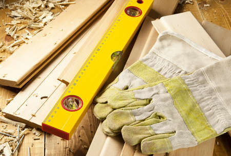 Carpenters level, nails and work gloves are on a wooden planks Stock Photo