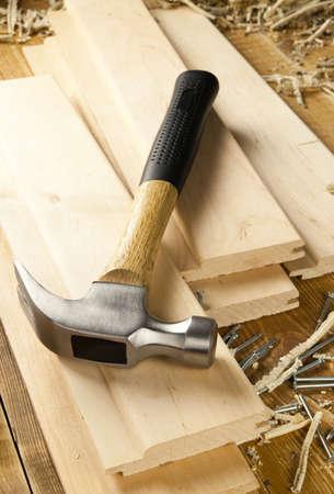 herramientas de carpinteria: Martillo y clavos se encuentran en una tablas de madera