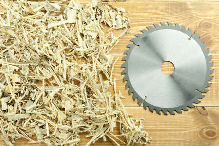 Circular saw blade on a wooden and sawdust background photo