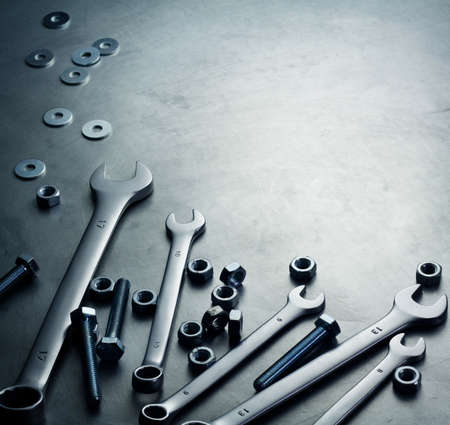 Wrenches, nuts and screws on a metal plate photo