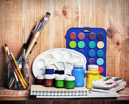 paint palette: Paintbrushes, watercolor, gouache and paper are on wooden shelf