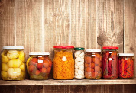 pickled: Preserved  autumn vegetables on shelf near a brown wooden wall