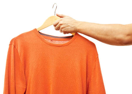 men hand holding hanger with t-shirt photo