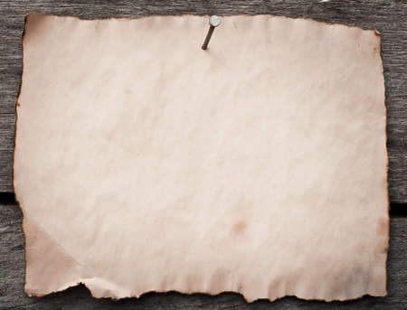 Old paper nailed to a grunge wooden background