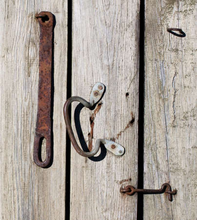 pawl: Rusty metal hook in old wooden door