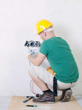 electrician with multimeter checking voltage photo