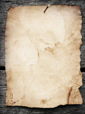 Old paper nailed to a grunge wooden background photo