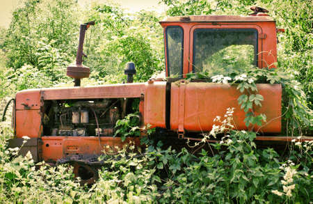 old tractors: Abandoned tractor in the grass Stock Photo