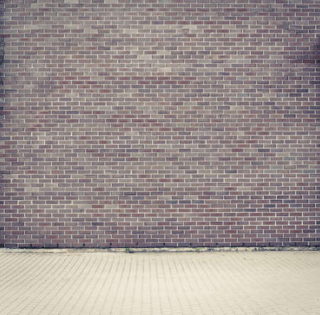 Brick grunge weathered wall background with walkway photo