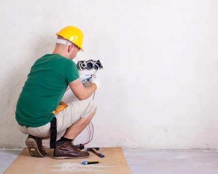 ingeniero electrico: electricista con multímetro control de tensión Foto de archivo