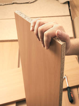 rearrange: Carpenter hand holding plank and mounting brown wooden furniture