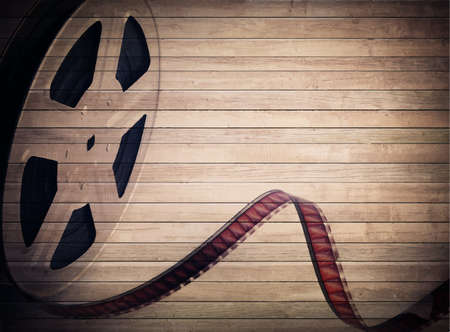 motion picture: Grunge old motion picture reel with film strip on brown wooden planks. Vintage background Illustration