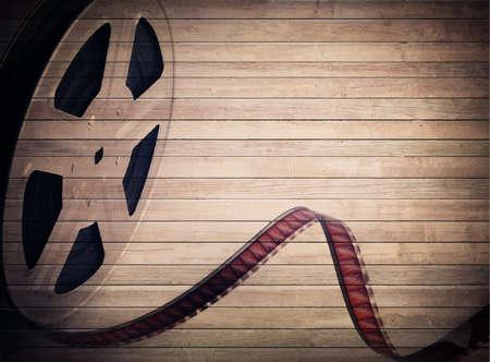 cine: Grunge old motion picture reel with film strip on brown wooden planks. Vintage background Illustration