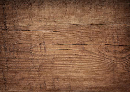 surface: Dark brown scratched wooden cutting board. Wood texture