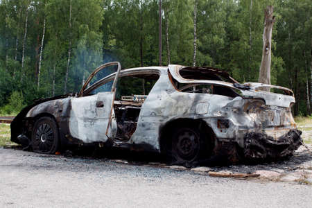 joyride: Burnt out rusted old car near the road and forest.
