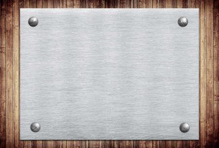 Metalen bord, naamplaatje op houten wand planken.
