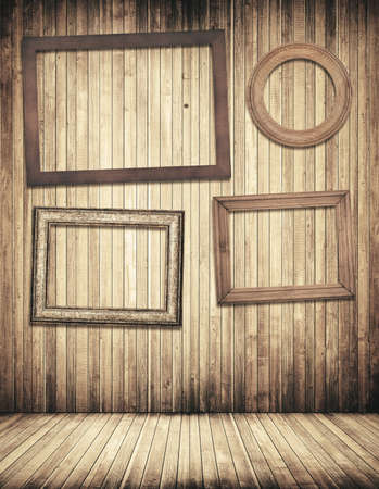 vintage frame: Wooden picture frames hanging on brown planks wall with old pine, fir floor.