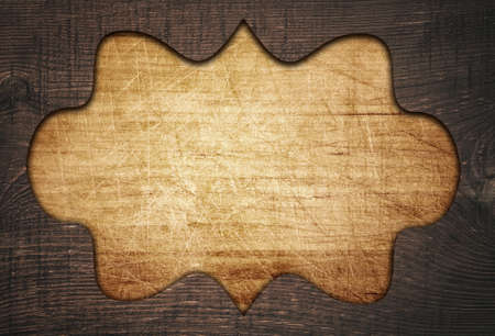 fretwork: Dark brown ornate wooden frame, fretwork on old scratched cutting board. Stock Photo