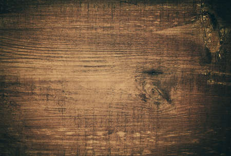 board: Dark brown scratched wooden cutting board. Wood texture.