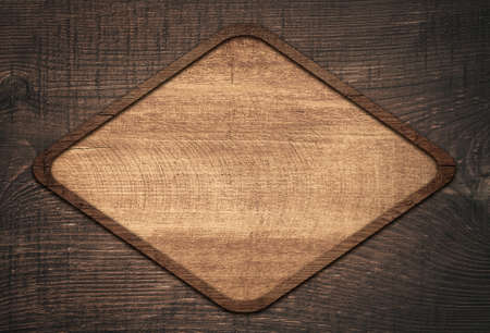 lozenge: Brown wooden lozenge with frame on dark wall. Stock Photo